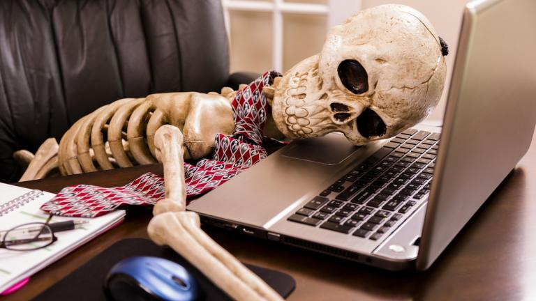 skeleton laying on laptop