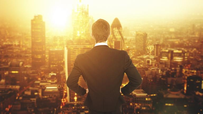 businessman staring at the citiscape sunset