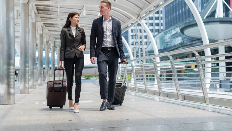 business people walk with luggage through an airport