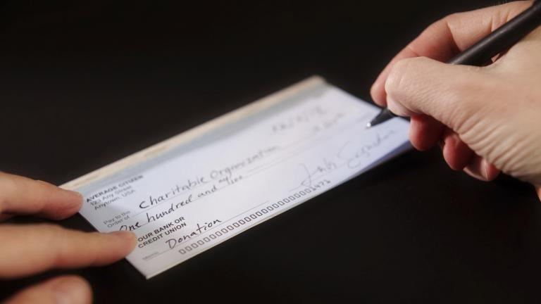 man writing a charity donation check