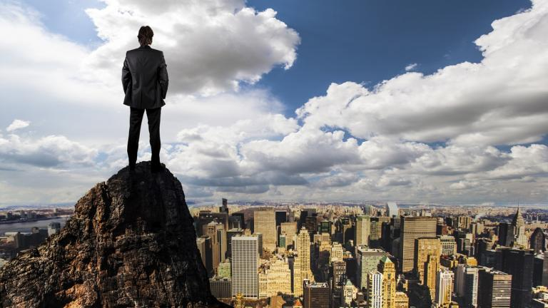 man standing on cliff looking over a city and clouds