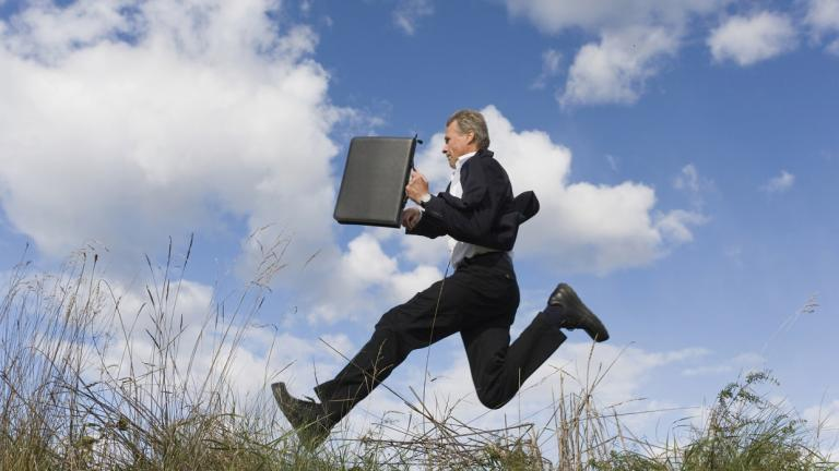 business man leaping through a cloudy field