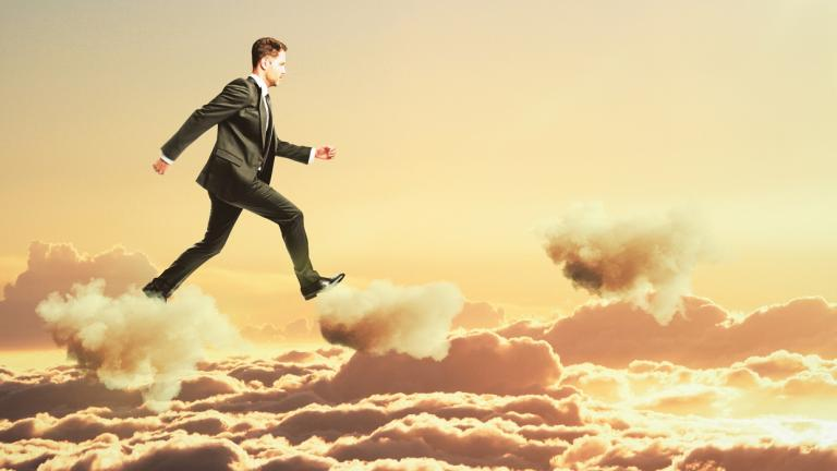 business man walking on clouds