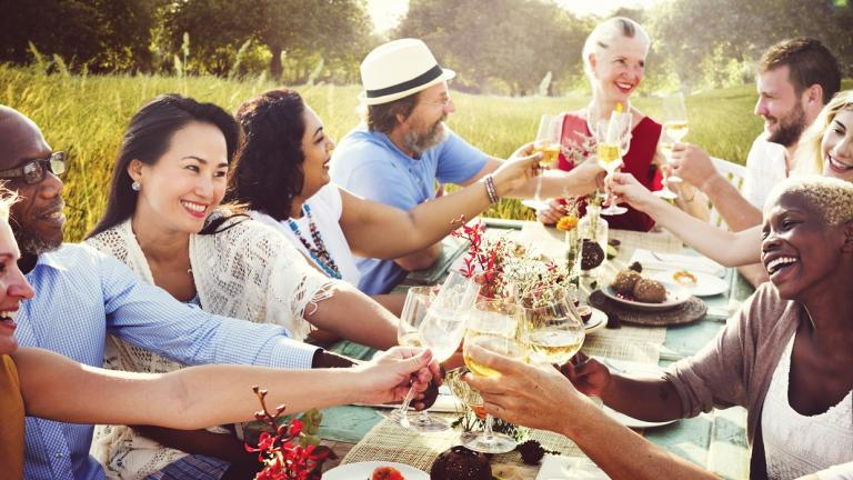 diverse people dine at outside table