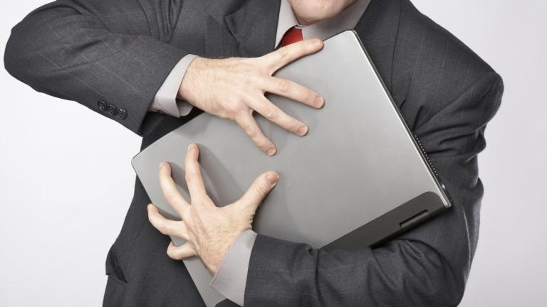 man clutching laptop