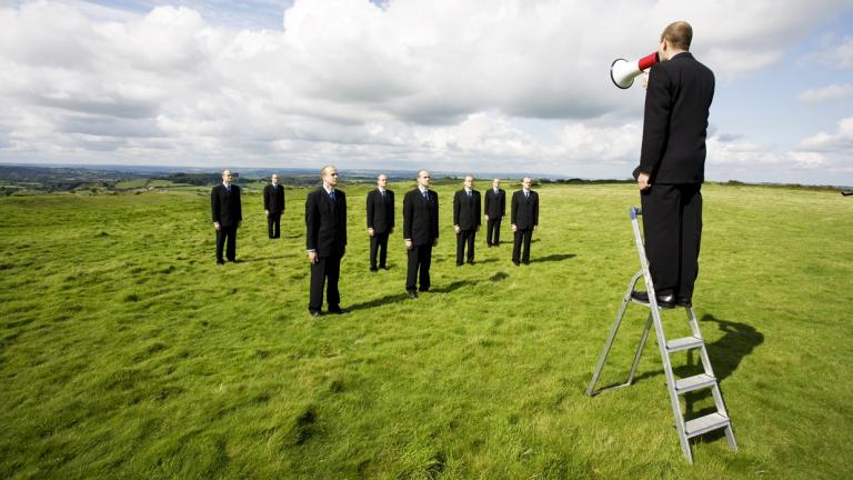 man on ladder yelling at other businessmen in a field