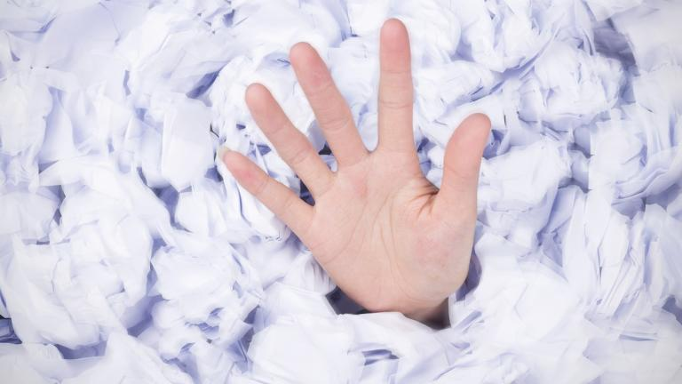 hand reaching out from under piles of paper