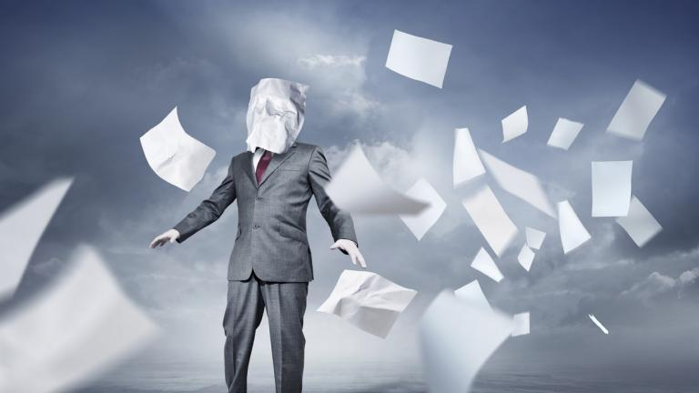 man surrounded by blowing paper