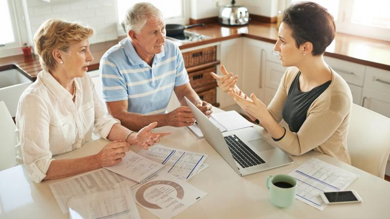 older couple conversing with businesswoman