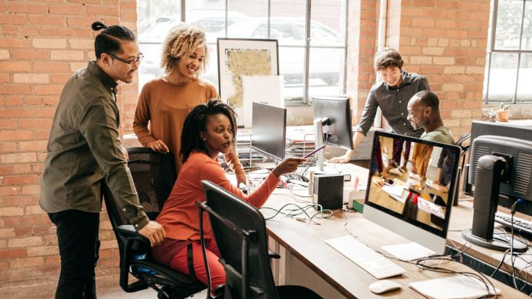 office workers in discussion around computers