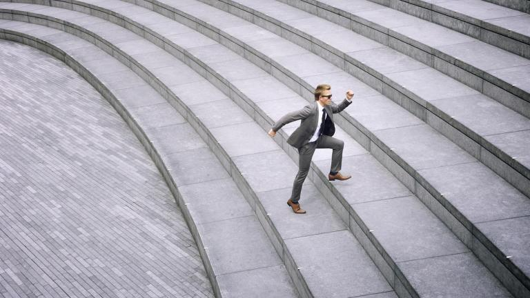 business man running up large steps
