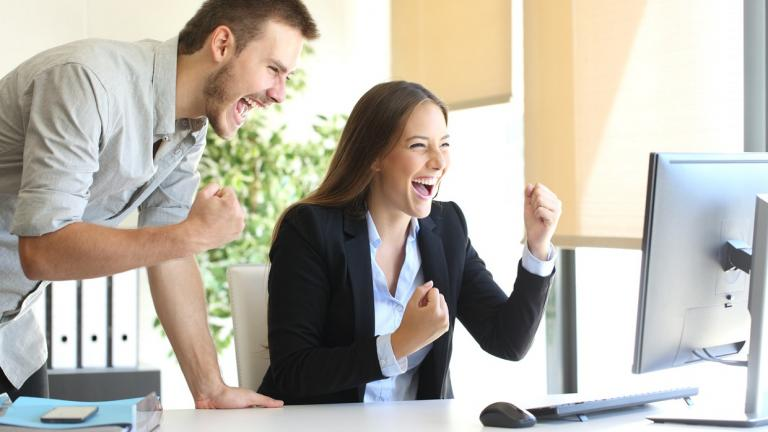very happy business people at a computer screen