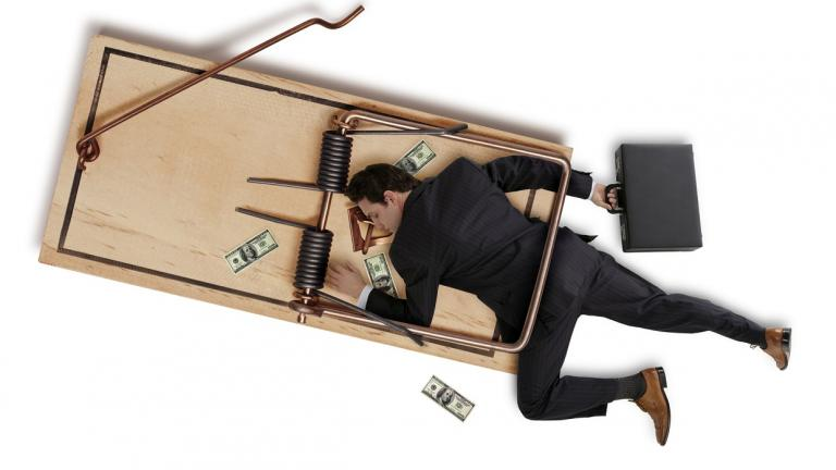 businessman caught in giant mouse trap