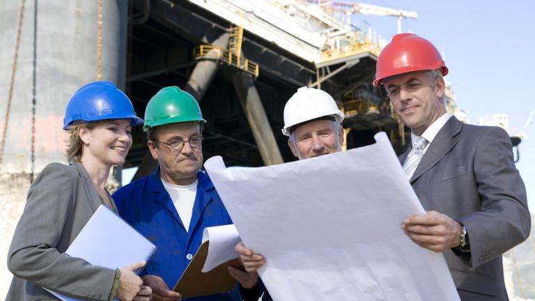 oil and gas workers look over plans
