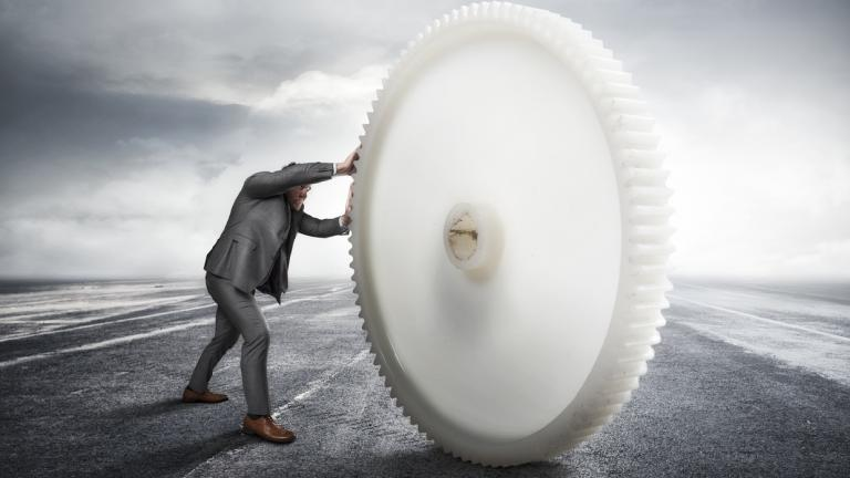businessman moving a large cog