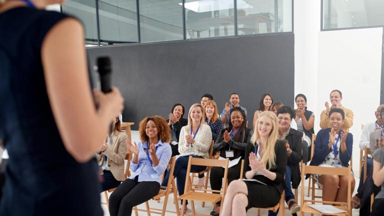 woman speaks in front of seated group