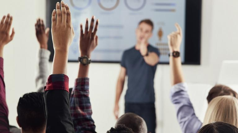 people raise hands in meeting