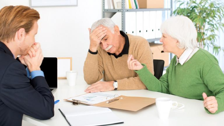 concerned elderly couple in meeting