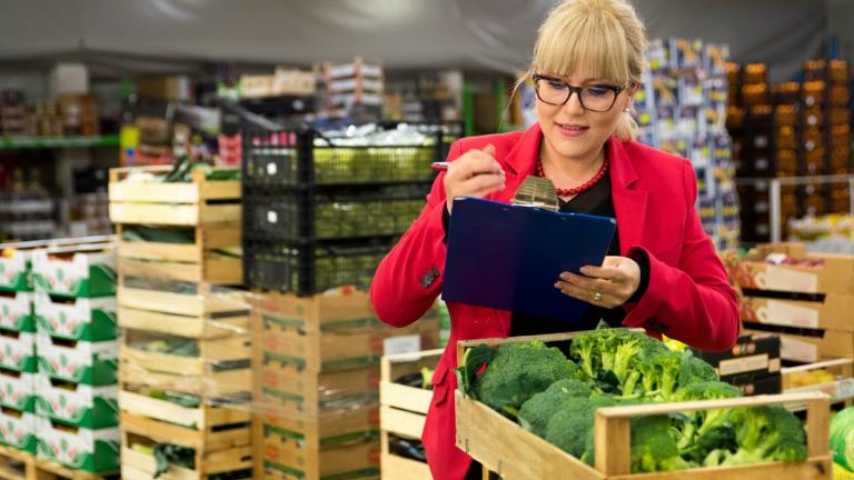 woman in food warehouse writing on clipboard