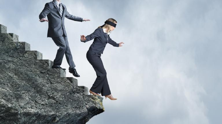 business people walking blindfolded down a cliff