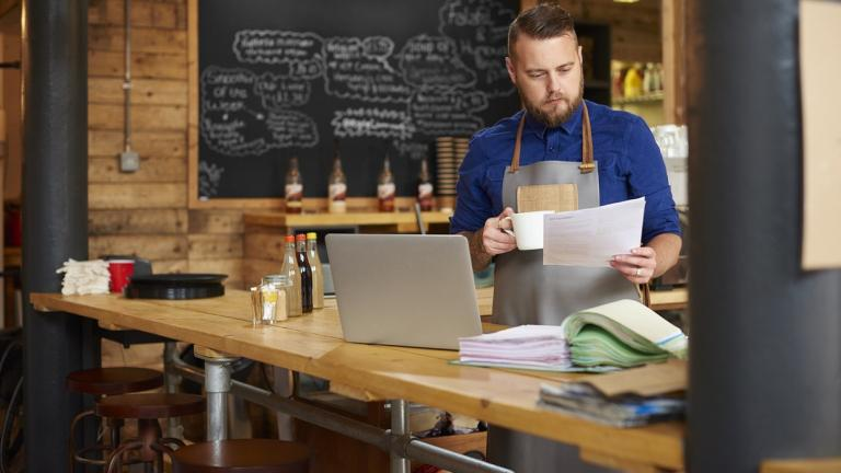 man in coffee shop looking at paperwork