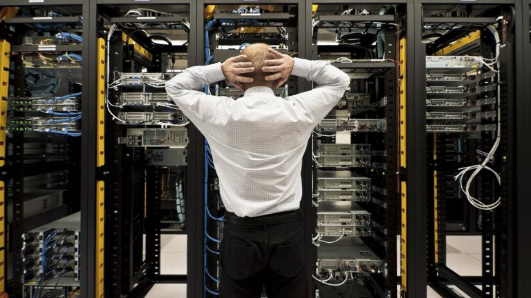 man in front of server stacks