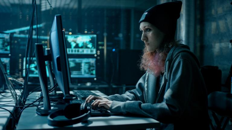 woman in dark server room on a computer