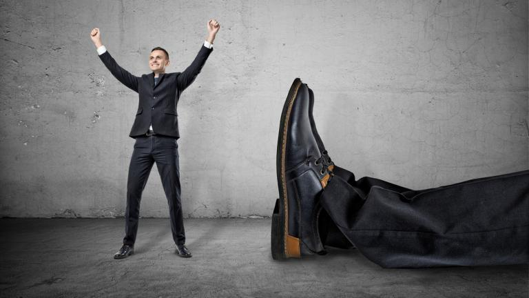mall businessman standing with his arms up near giant leg