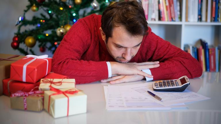 sad man with presents looking at papers and calculator