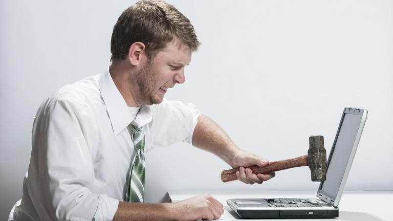 man hammers laptop