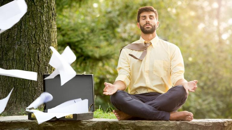man meditating as paper blows