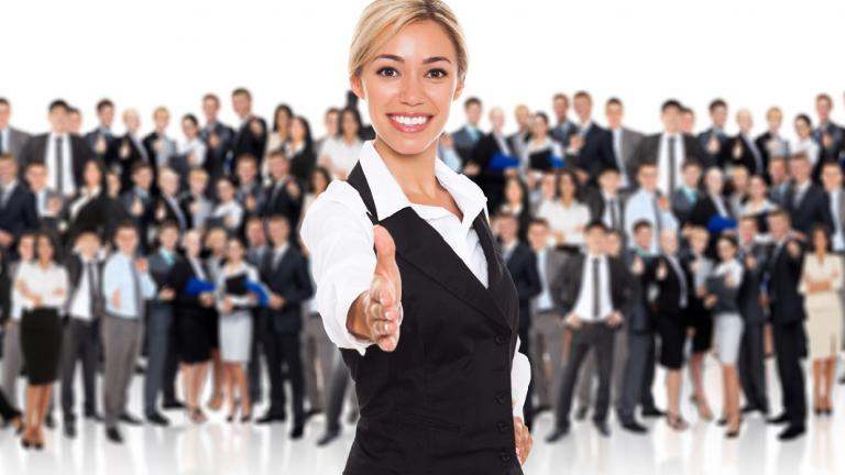 young businesswoman extending hand in front of large group