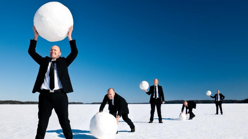 men in suits roll large snowballs