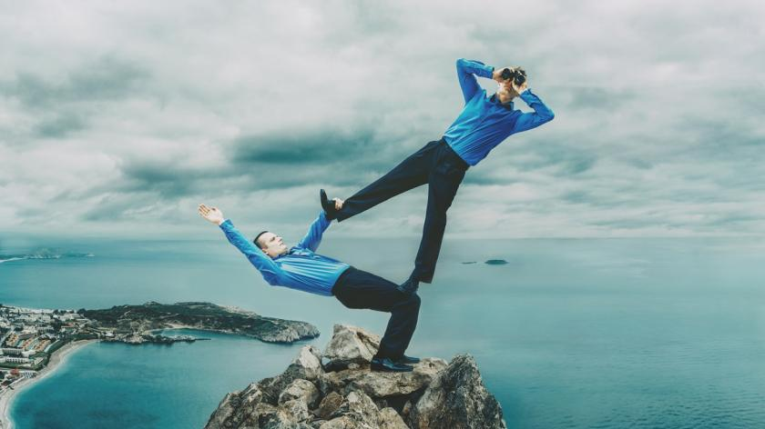 businessmen balancing on a cliff