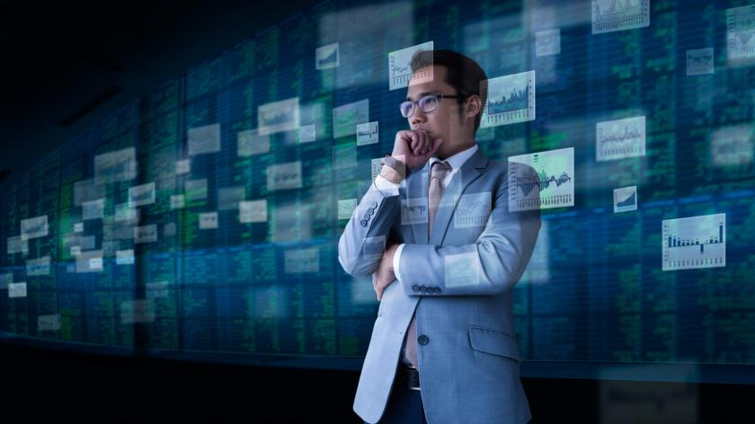 business man surrounded by screen images