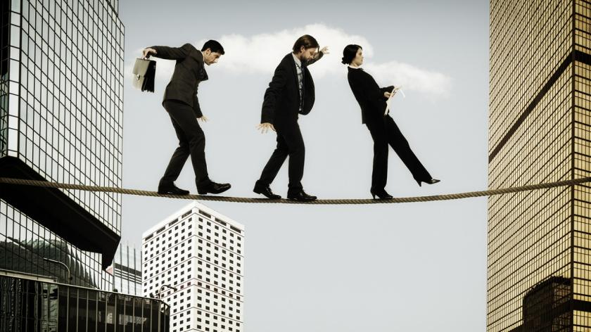 business people walking between buildings on a rope