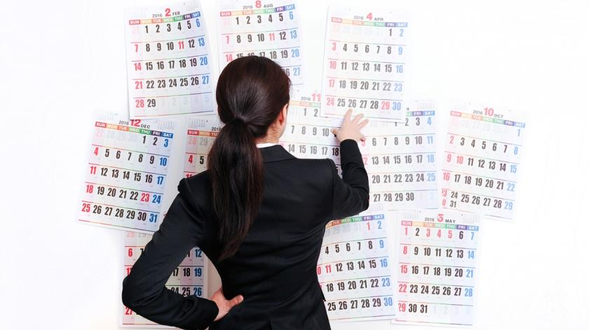 business woman in front of calendars on a wall
