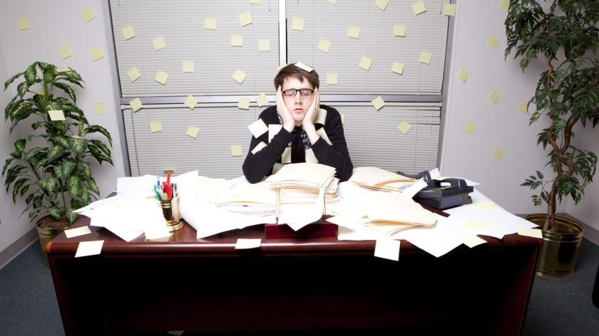 man at desk covered in papers and post-its