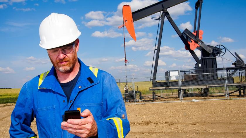 man on mobile phone in front of oil rig
