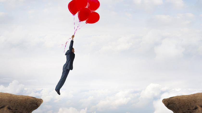 person floating between cliffs holding balloons