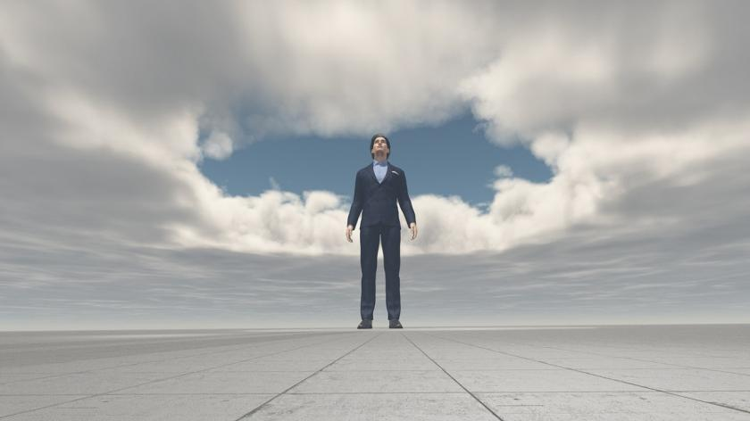 man standing under cloud opening