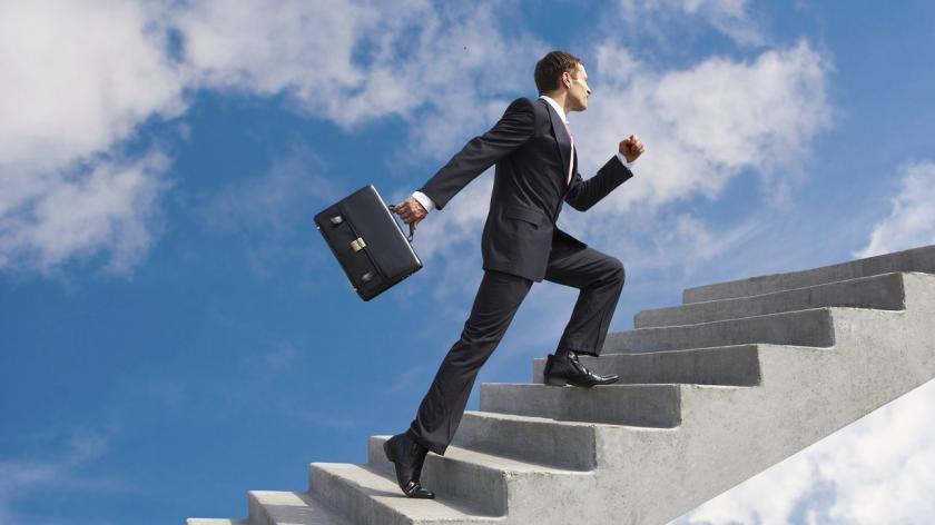 businessman walking up steps into the clouds