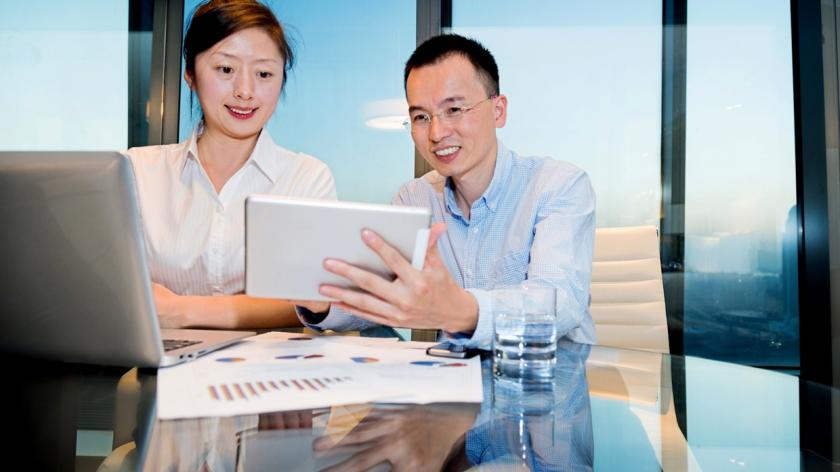 man and woman look at tablet in boardroom