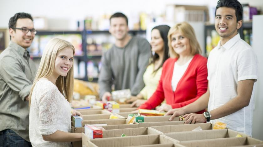 people helping to fill boxes of food