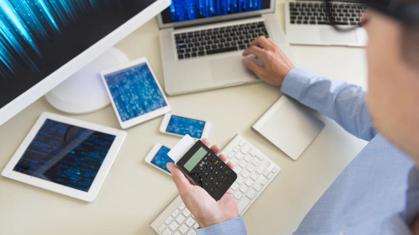 person with multiple devices on their desk