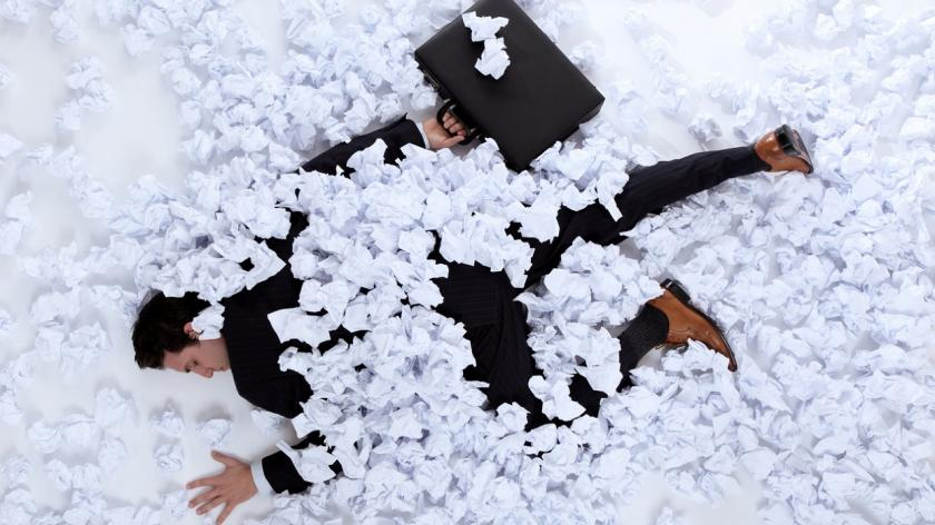 businessman laying under balls of paper