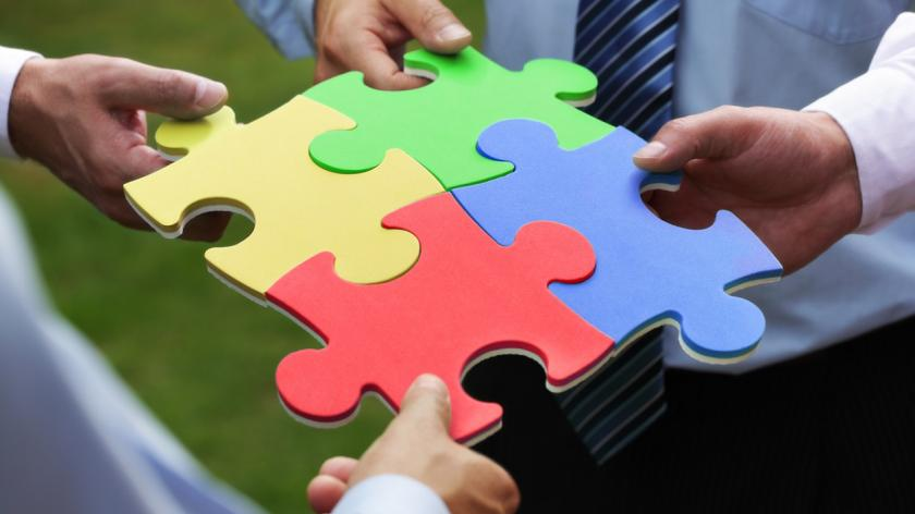 people holding colored puzzle pieces