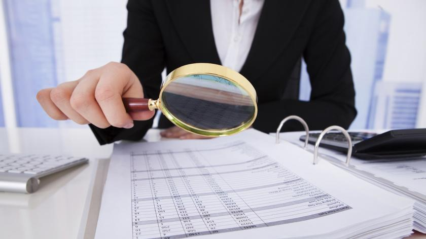 woman looking at expenses with magnifying glass