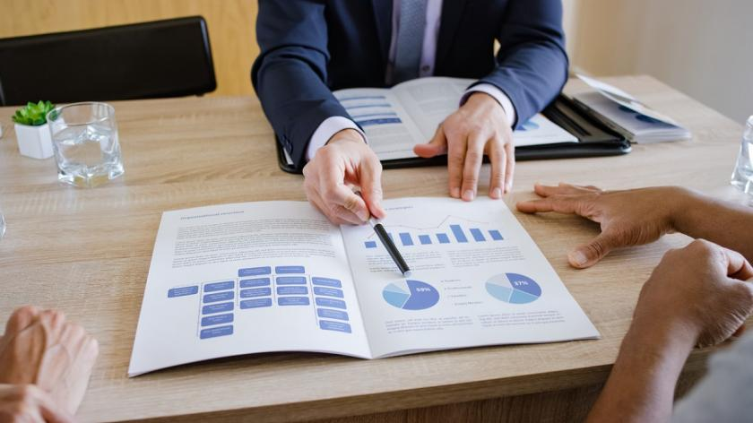 financial planner pointing to forecast sheet
