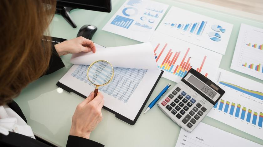 woman looking at financial docuents with magnifying glass